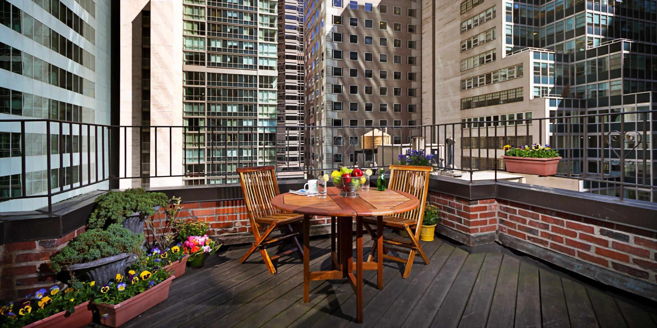 outdoor terrace with table overlooking the streets of manhattan