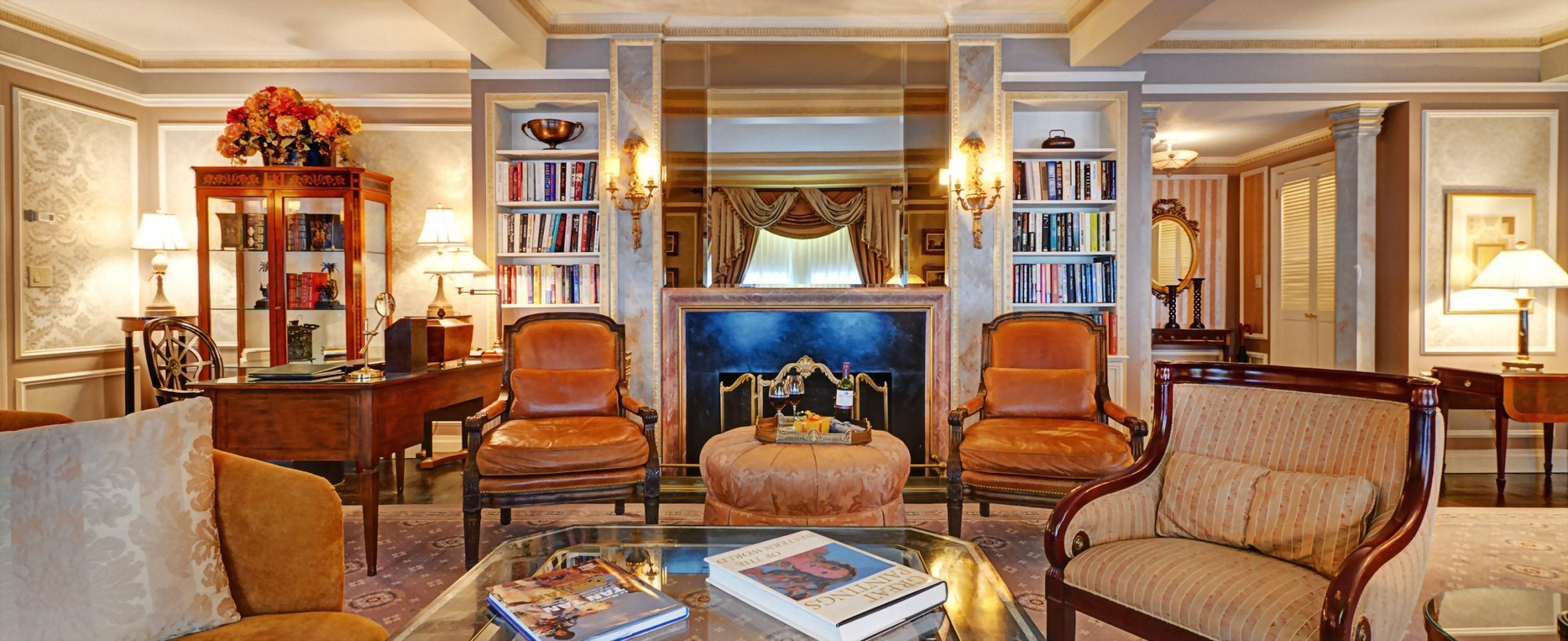 The living room of the Presidential Suite honoring Vaclav Havel boasts a faux fireplace, a baby grand piano, and large dining table.