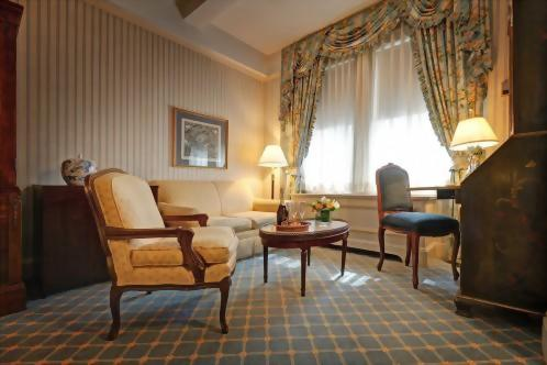 Most of the Deluxe Queen rooms at the Hotel Elysée have sitting areas with a couch, chair and a coffee table.