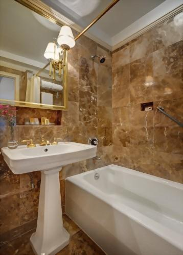 Typical guest room bathrooms at the Hotel Elysée are decorated with marble and pedestal sinks.