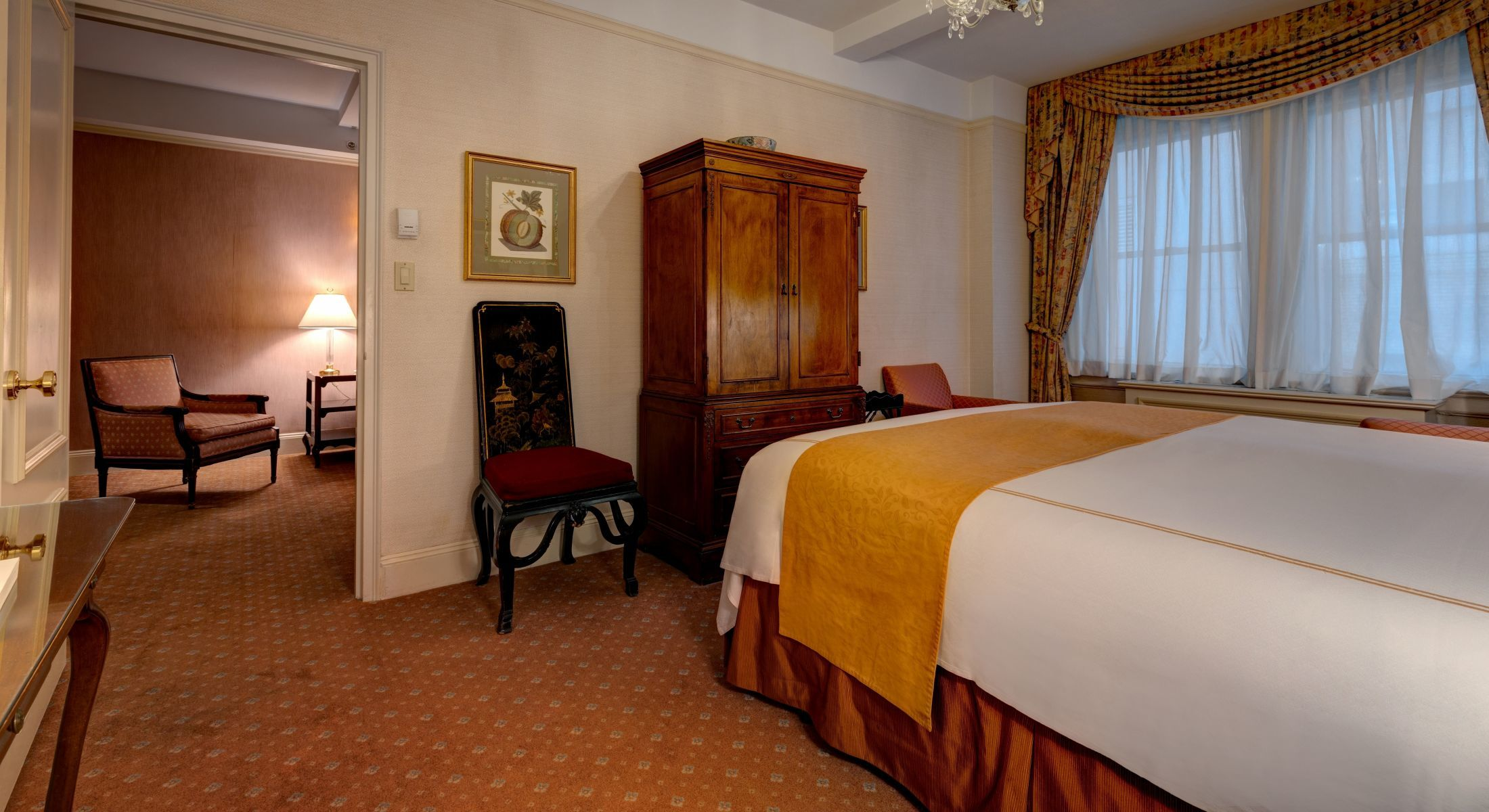 Bedroom of the King Suite at the Hotel Elysee with king bed and armoire.