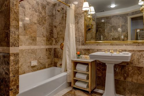 Each room at the Hotel Elysee is equipped with a classic marble bathroom.